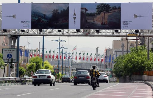 Cars drive past billboards in the Iranian capital of Tehran displaying art pieces from local and foreign artists. (Atta Kenare/AFP/Getty Images)