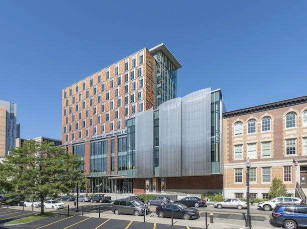 The base of the Student Life and Performance Center aligns with the cornice of the adjacent St. Botolph Building, which houses the NEC Opera Department. The seven-story residential tower is clad in offset, operable windows and variegated terracotta tiles applied in mixed, rhythmic patterns. Expansive glazing at the lower levels erases the boundary between the street and interior spaces. The performance podium shimmers with stainless steel screen cladding and offers tantalizing glimpses of the...
