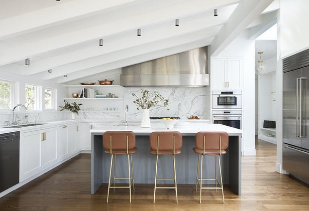 Jennifer Jones of Niche Interiors paired the cool hues of the kitchen's Caesarstone counters and stainless hood with leather upholstered Petra stools by Thomas Hayes Studio.