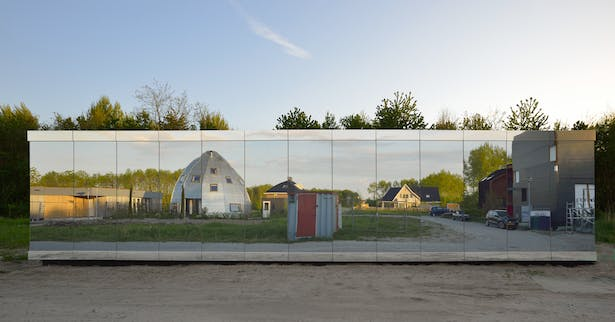 The street facade has a secret window behind the glass panels, with a view of the street and neighboring plots