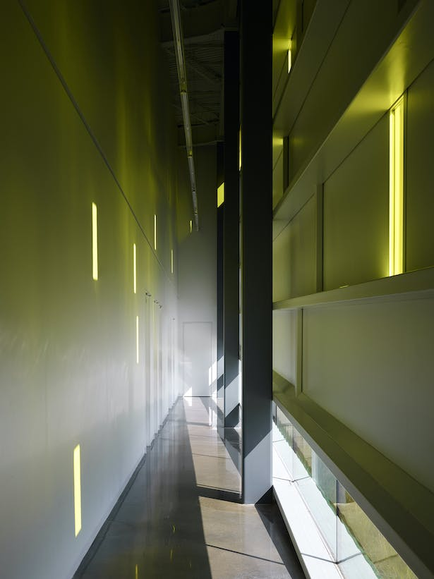 "The west/secondary gallery corridor provides access to toilets, the green room, and administrative offices. The afternoon sun projects ever-changing gold ""notes"" onto the wall. ""Notes"" appear, move, change and disappear during the day capturing the kinetic energy within the space. The glass at the floor line suggests the building is buoyant."