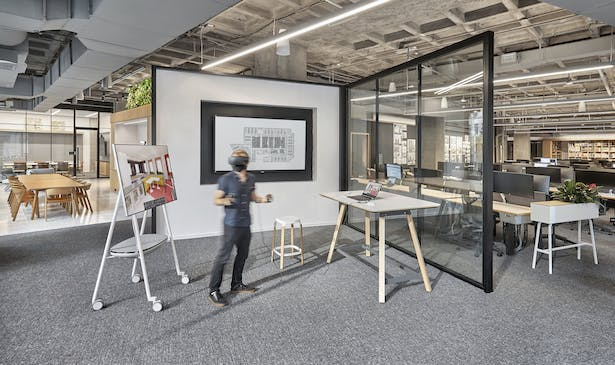 Visible from the street below, an area known as 'The Cube' functions as a flexible and centralized space that gives the neighborhood a peek into the studio's design process. Photo Credit: Garrett Rowland