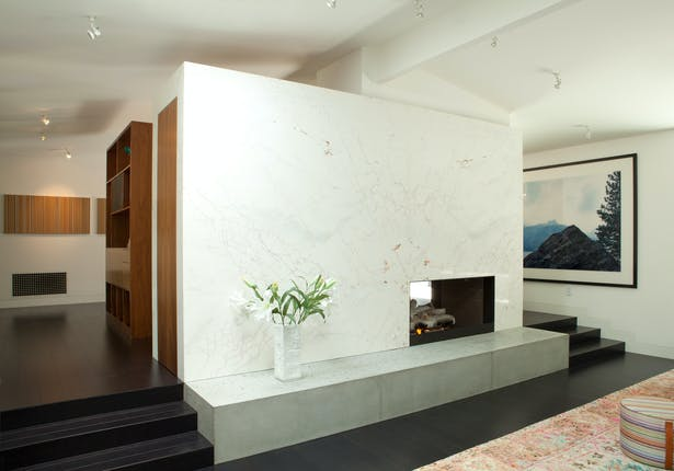 A new double sided fire-place divides the living and dining areas, and negotiates the drop in level between those two rooms. The stone is Italian dolomite, the hearth is solid poured concrete and the firebox is framed in blackened steel.
