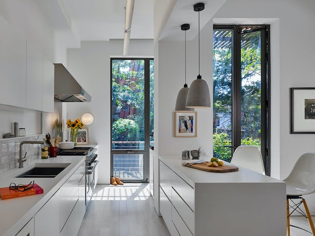 Sun-filled kitchen with french doors and clean white cabinetry leads out to the patio.