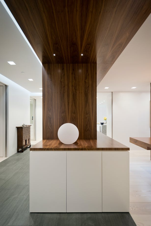 A Walnut Portal Creates a Threshold from Entry to Living Space