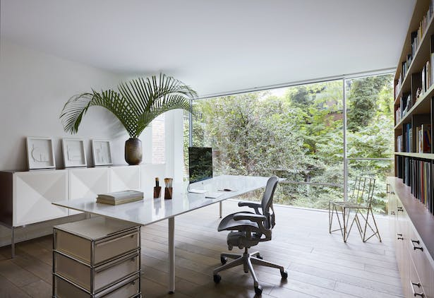 The spacious home office occupies a mezzanine that has been cantilevered over the garden.