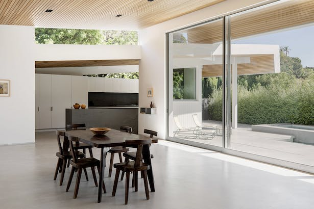 'Inside, the butterfly roof marks much of the interior as well, with ceilings clad in the same cedar siding. A fireplace originally divided what is now one large, open great room complete with expansive sliding glass doors that overlook a patio and pool.'