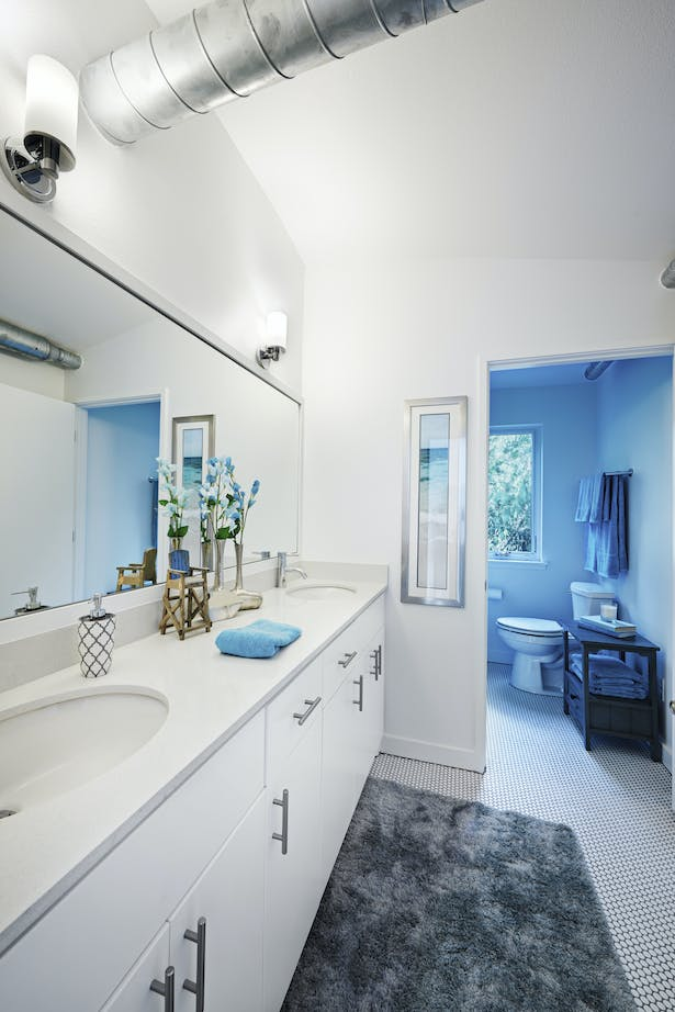 This basic bathroom layout is simple by design, but cohesive in material selections, and allows plenty of natural light via its window that looks onto an undevelopable forested property directly next door.