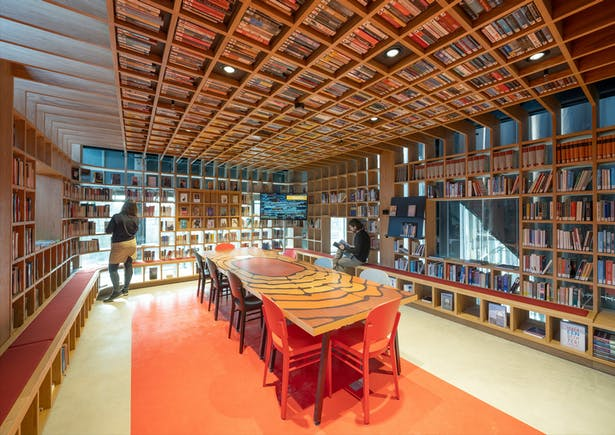 In the intimate Writing Room, books continue seamlessly from the walls onto the ceiling, wrapping the entire space and turning it into an immersive world of literature and language.