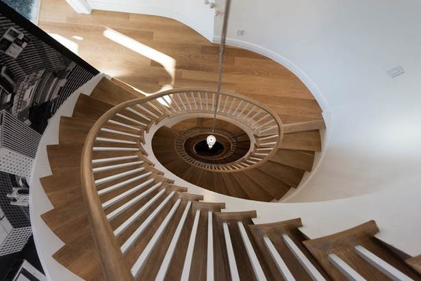 Elliptical wooden stairs topped with a skylight