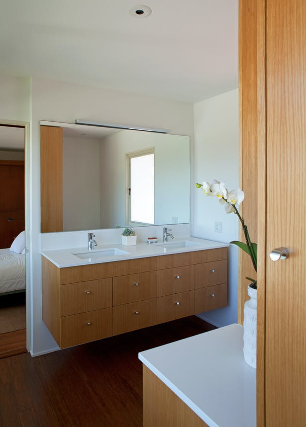 The bathroom attempts to complement and respect the original aesthetic of the house by incorporating floating volumes and spaces envisioned by Harwell Hamilton Harris.