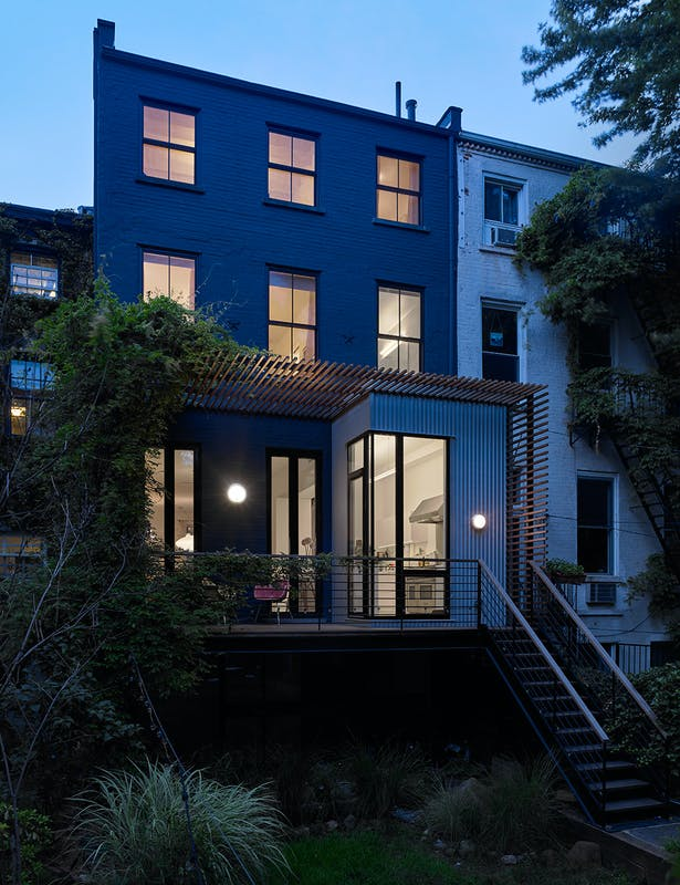 The rear extension adopts a more industrial material palette with stained black metal windows and doors, dark wood decking