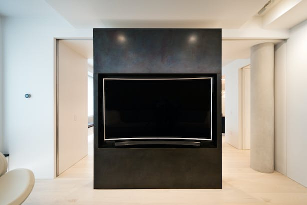 Glass Doors Pocket into the Black Steel Volume to Separate the TV Room from Living Space