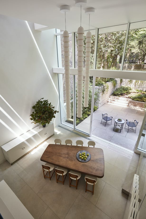 The seamless connection between inside and outside is due to the continuity of surfaces and sliding doors that offer uninterrupted access to the garden from the open kitchen and dining area on that level.