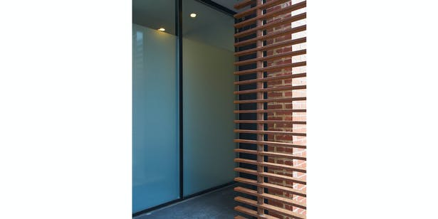 Custom steel entry louver with storefront behind.