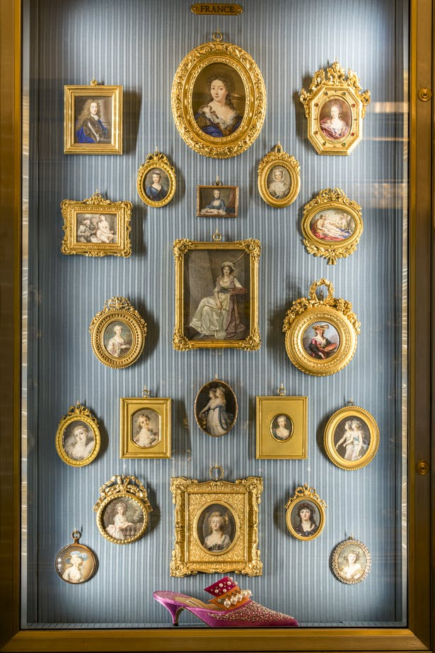 A number of shoes are situated within miniature portrait cabinets