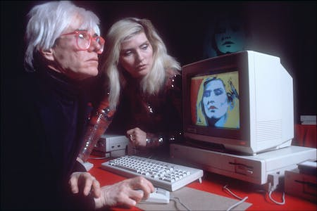 Andy Warhol demonstrating the Amiga PC in 1985. Image via Wikipedia Commons.