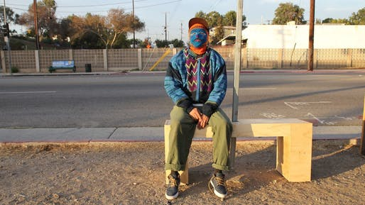 The anonymous artist sitting on a bus-stop bench he installed. Photo credit: Carolina A. Miranda/Los Angeles Times.