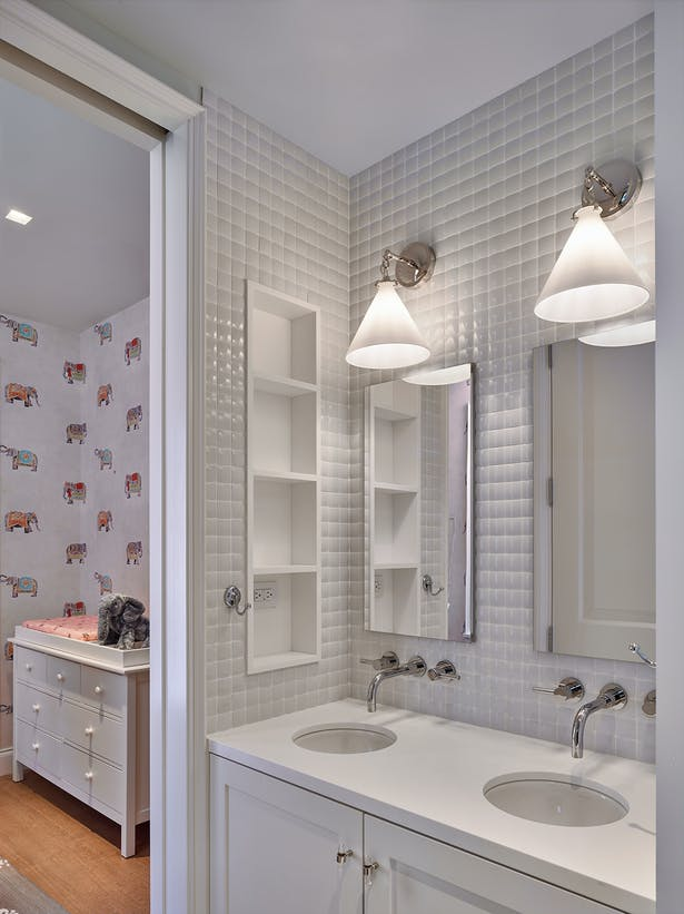 The children's bathroom is a fresh white with built-in storage.
