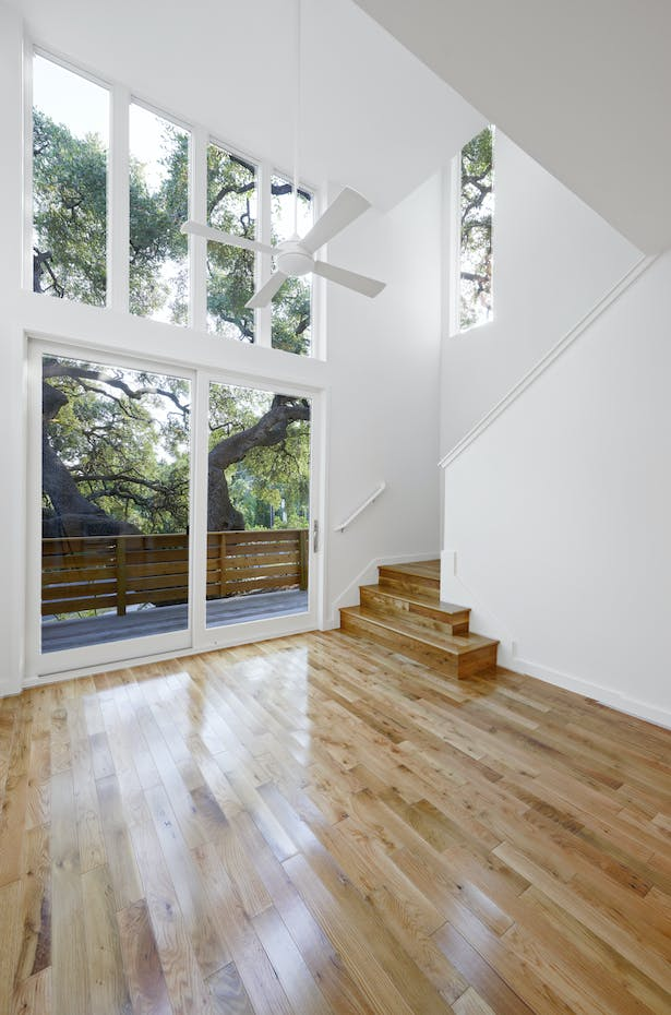 The balcony of House 1 is close enough to the 400 year-old oak to climb on to the tree. This house is only a few feet from the street. The guardrail and the tree shield the occupants from the street. The pecan flooring was chosen for its durability and is a nod to the Central Texas environment (remember, pecan is the Texas state tree).