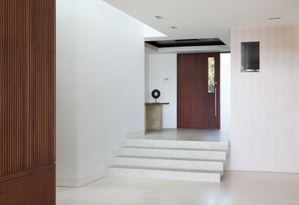 The entry vestibule is a polishes concrete floor that cascades down into the public rooms. A perimeter skylight allows sunlight to wash the wall. Recessed base boards reinforce the simplicity of the walls.