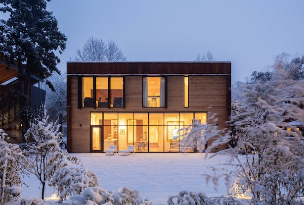 Warm light glows through the modern addition's extensive glazing on a snowy evening.
