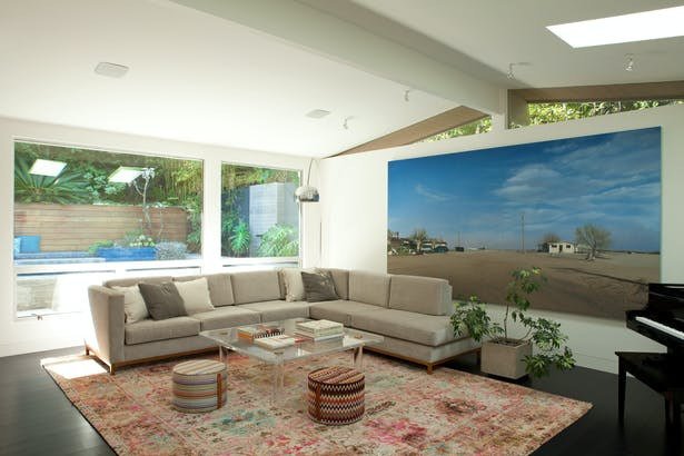 Living room, with large windows looking out to the rear gardens and pool.
