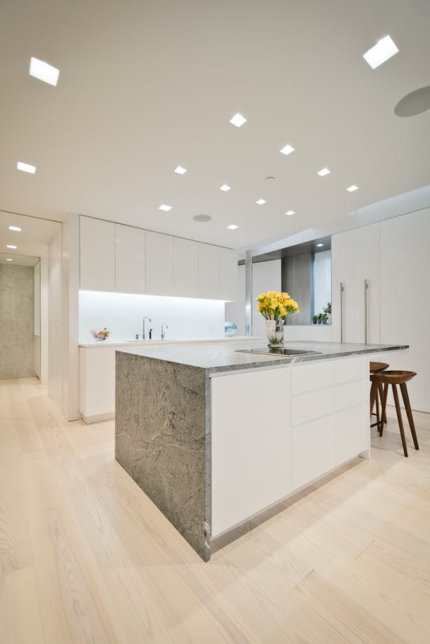 A Marble-Wrapped Island Adds a Natural Element to the Minimal White Kitchen