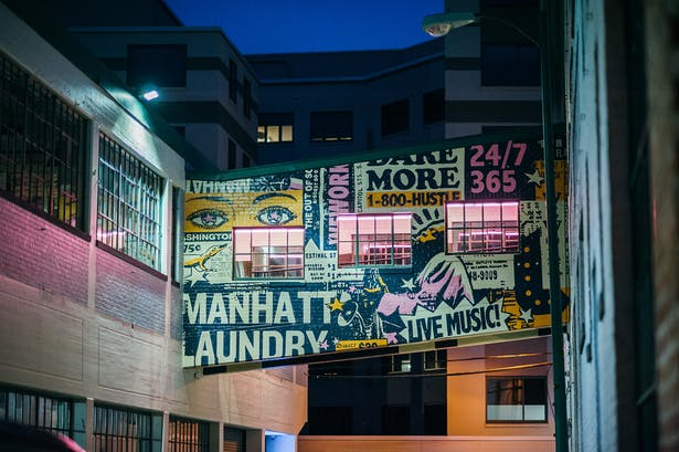 Sky bridge mural referencing the building name, local gogo-music flyers, and WeWork branding