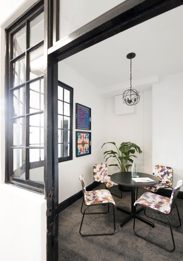 This intimate meeting room was created from another existing storage space. The window frames were painted black in keeping with the steel exterior windows. A modern patterned velvet makes a bold statement against the neutral Interface carpet tiles, while the game boards and new iron fixture hint at elements in the other rooms.