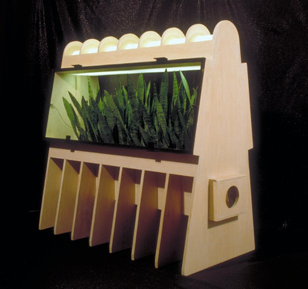 A Bio Filter and light combination, 1990. The plants are used to help purify the indoor air of a house or office. The indoor air is drawn into the bio-filter with a small fan where the leaves of the plants pull pollutants out of the air before it is blown back into the room..