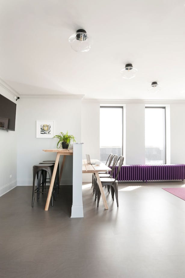 """Toward the front of the room, an awkward notch in the wall creates an opportunity for a semi-enclosed work space. Buzzi space """"picnic"""" tables at offset heights provide two layers of function paired with seating in an iron black. The half-wall is capped with the same violet veined marble."""