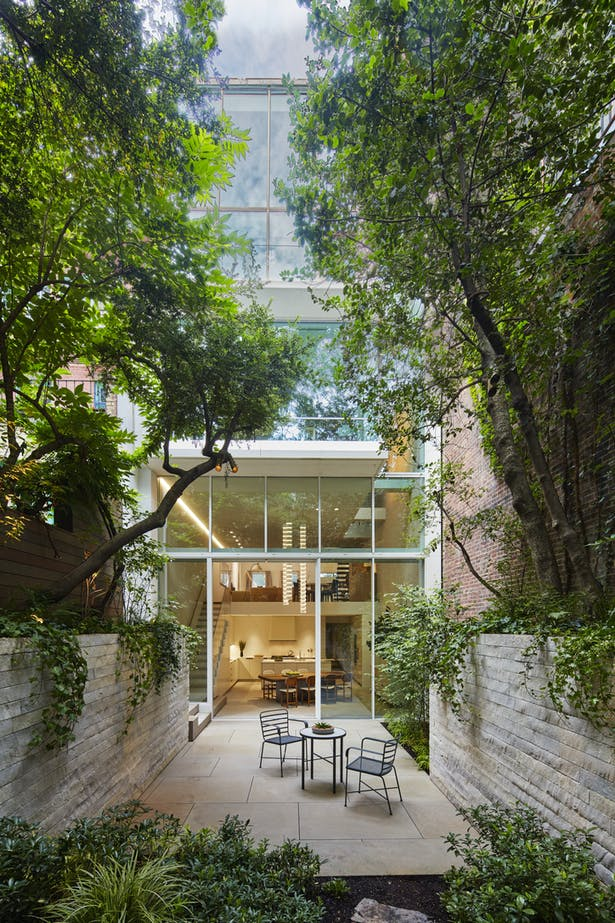 A five-story glass façade opens the house's living spaces to the rear garden and the sky.