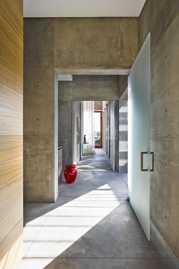 Passages through a hallway within the volumes allow for strong lines of light to permeate.