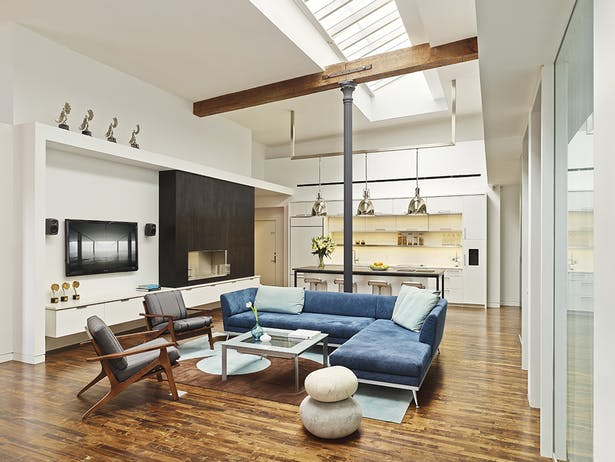 The focal point is the open lounge/kitchen area designed to maximize the loft design, showcasing the building's original skylights, wood beams, brick walls and cast-iron columns.