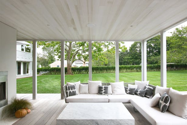 A Screened Porch, with the Screens Removed, is More Adult-Oriented with Casual Seating Around a Fireplace and a Large Outdoor Dining Table