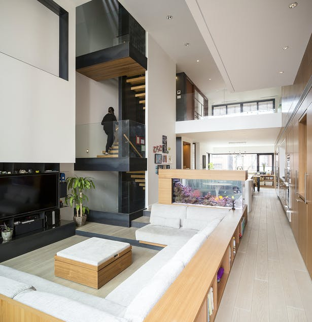 Double Height Living Space with Built-In Sofa and Aquarium with Playspace Mezzanine Above
