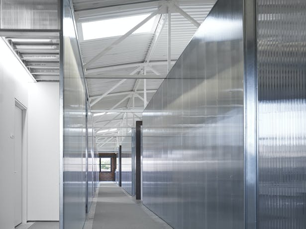 The 2nd floor workspace corridor is asymmetrically placed in order to take advantage of the existing skylight locations. The polycarbonate is transparent, reflective and private all at once.