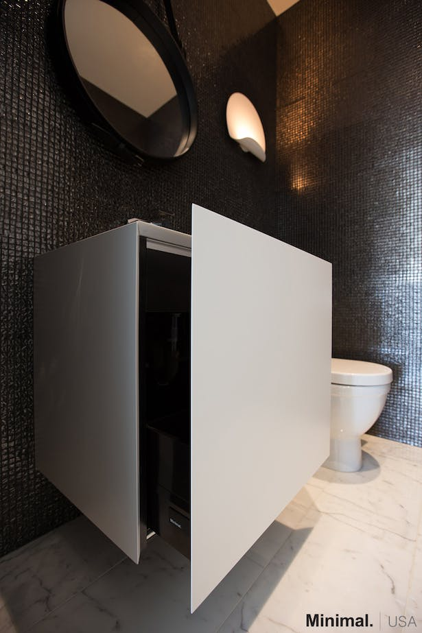 This sculpture-like cube vanity, in glossy white lacquer, not only enhances the elegance of the bathroom, but also is a sleek solution for giving more storage space, thanks to its opening bottom drawer with mitered 45° edge.