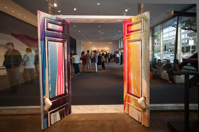 Visitors are welcomed in by the giant colorful McMansion doors that Koumoundouros refurbished surrounded by transparent walls. Photo by Marianne Williams.