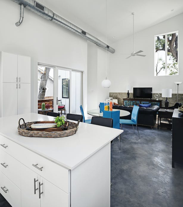The unapologetic use of cheap materials and finishes allowed for greater investment in the shape and form of the space, and placement of doors and windows. The framed view of a tree is displayed on the wall like a hung painting. A private balcony extends the dining and living space beyond the four walls.