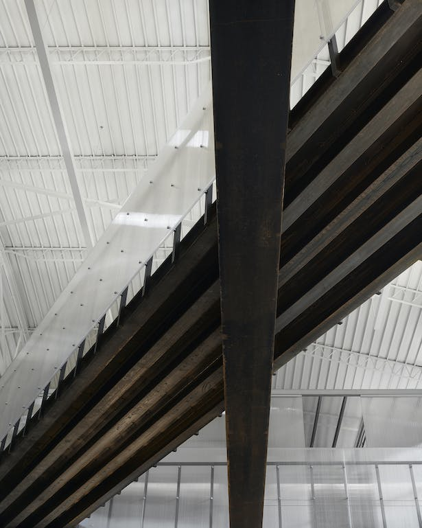 View from below of the new steel bridge and historic wide flange beam. We left the steel exposed and waxed it to keep it from rusting. The 1930s bowstring truss ceiling and deck is visible.