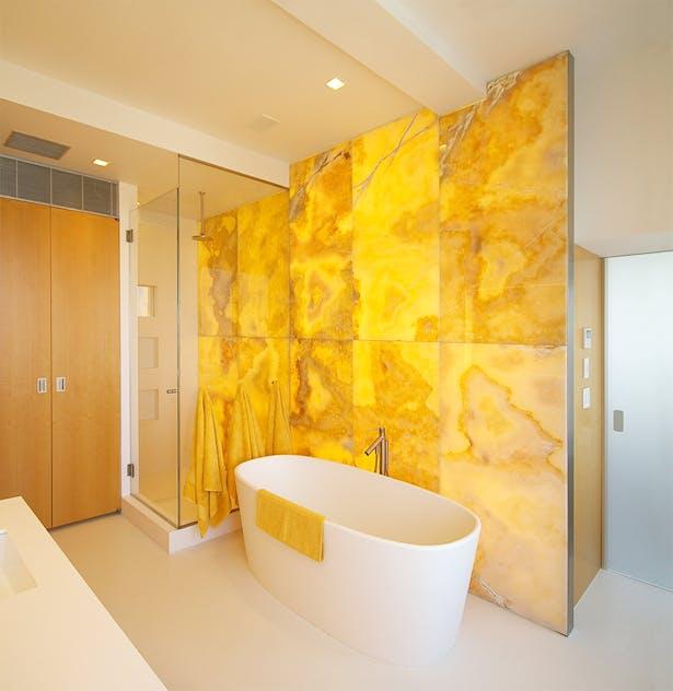 Glowing onyx wall warms the master bathroom