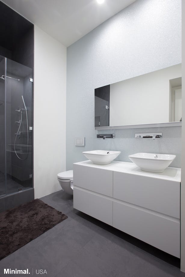 The large rectangular vanity, catches the eye with its horizontal groove in the middle and its mitered 45° edges which leaves open the drawers easily. The two large sinks are, this time, leaning against the top made in Corian.