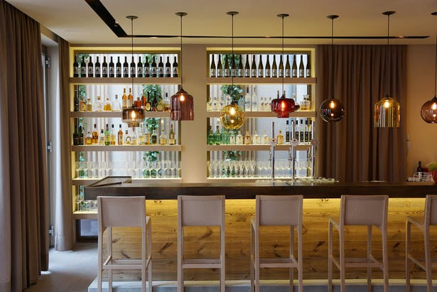 The bar, made of concrete, wood and hammered metal. Behind the rack the 'green' background of the vertical garden of the terrace.