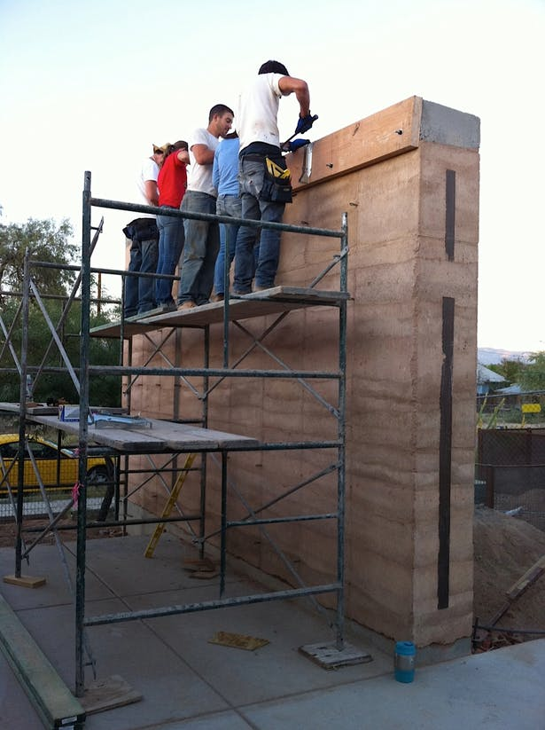 attaching ledgers for roof construction on completed rammed earth wall