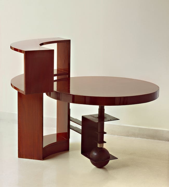 Table and bookcase (MB960), c. 1930, designed by Pierre Chareau, walnut and black patinated wrought iron; Bookcase: 36 1⁄2 × 45 1⁄4 × 8 in. (92.7 × 114.9 × 20.3 cm); table: 23 1⁄2 in. (59.7 cm) high, 33 3⁄4 in. (85.7 cm) in diameter. Vallois, Paris. Photograph by Ken Collins, image provided by Gallery Vallois America, LLC