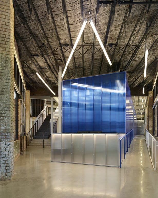 View from the flatiron entry towards the reception desk. The blue polycarbonate office core defines new vs. historic. The original exposed metal lath and concrete deck above remains. Floors are polished concrete.