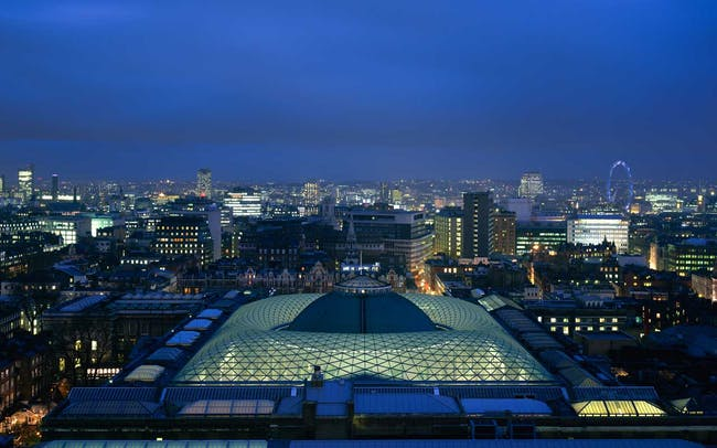 The glass canopy illuminated at night Image credit: Foster + Partners