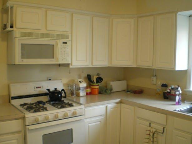 Kitchen BEFORE renovation - all white melamine, Formica, vinyl flooring and bad carpentry